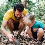 Vader en zoon zitten gehurkt beestjes te zoeken op de grond.