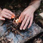 Twee handen maken met kleine twijgjes een vuurtje