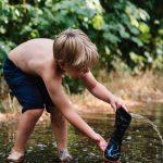 Een kind schept met een laars water uit de vijver