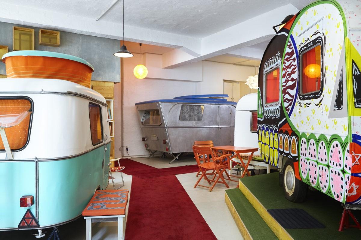Drie opgeknapte kleurige caravans in een hal