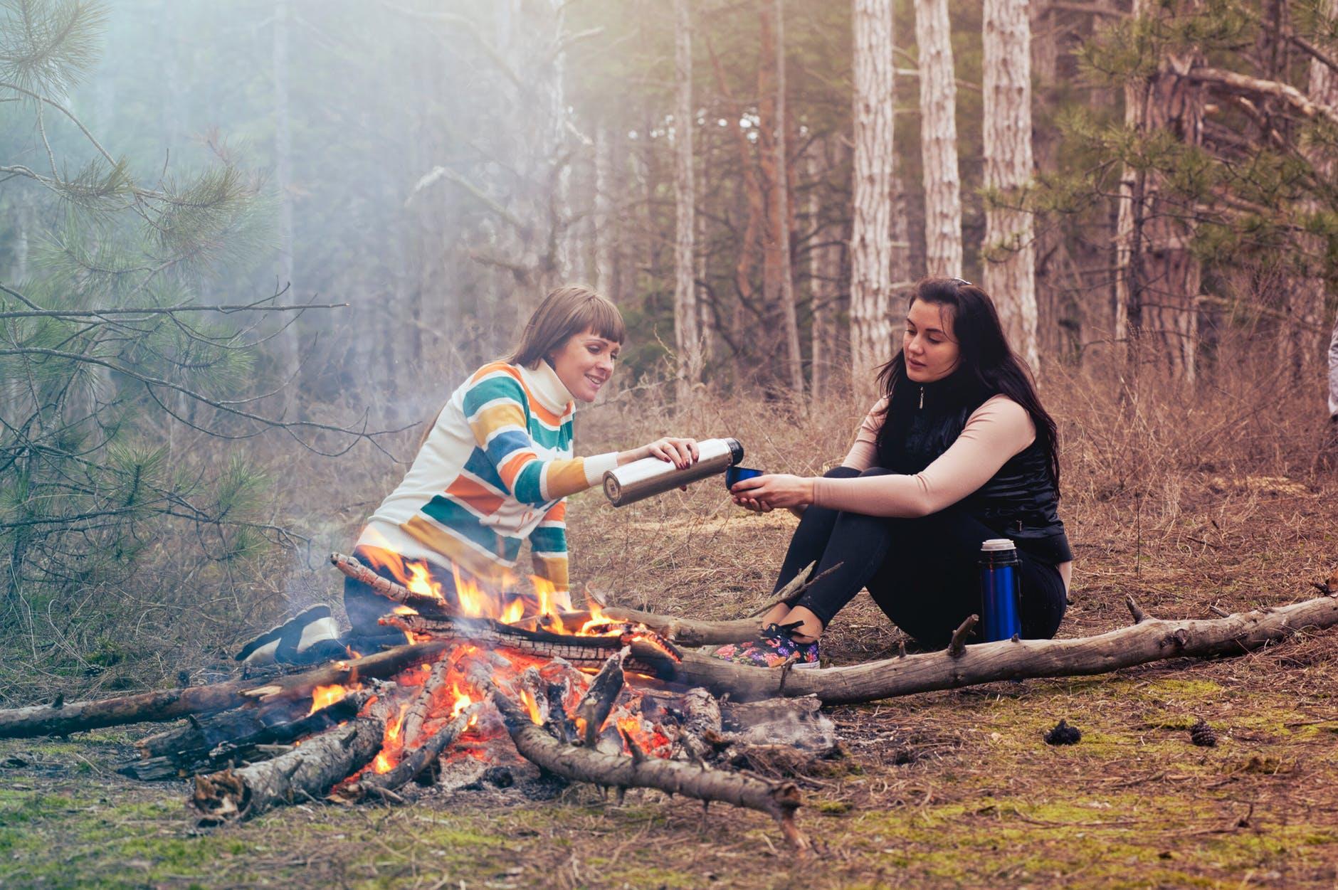 Twee vrouwen zitten bij een kampvuur en schenken een kop thee in uit een thermosfles