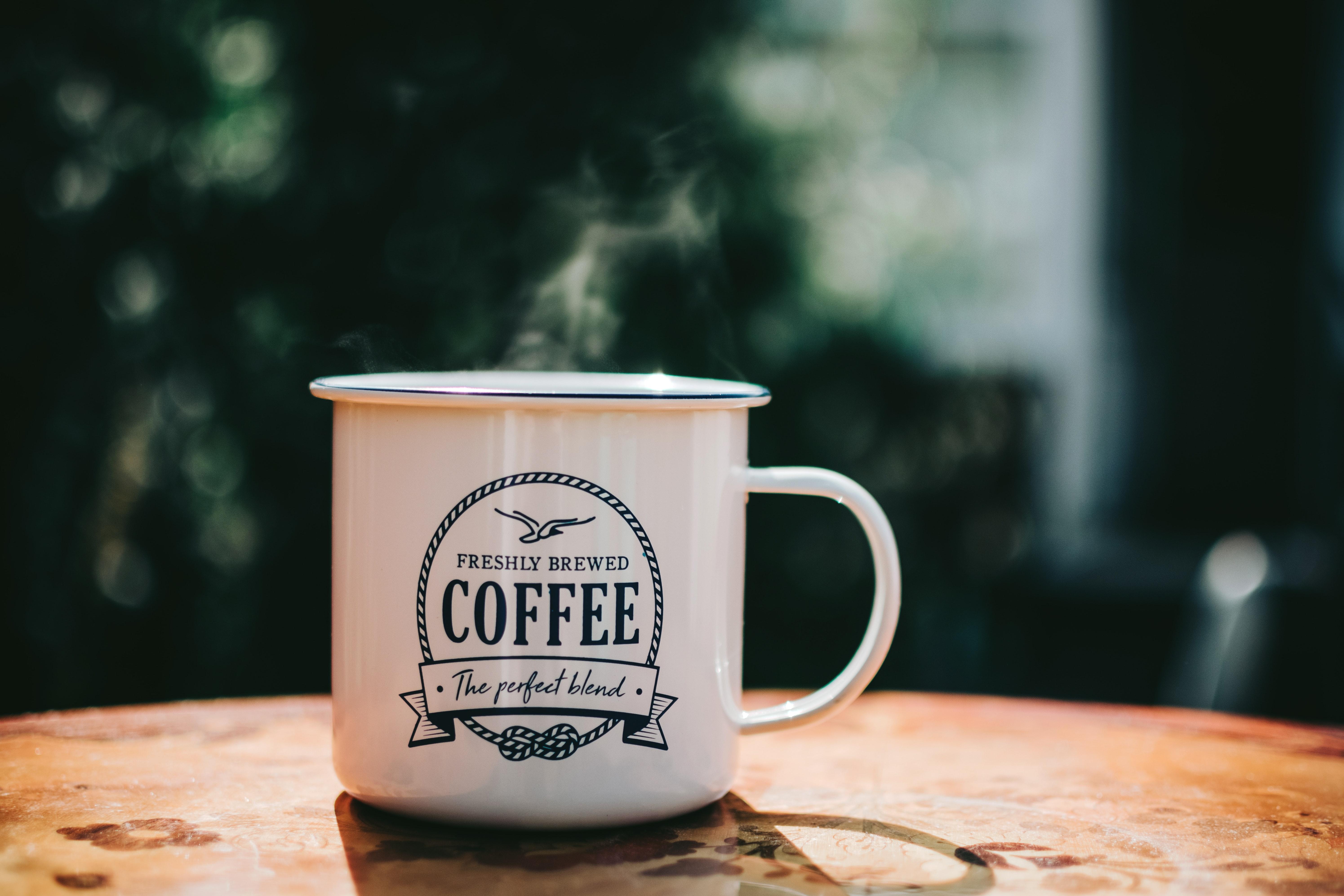 een witte emaille mok met daarop de tekst 'perfectly brewed coffee'.