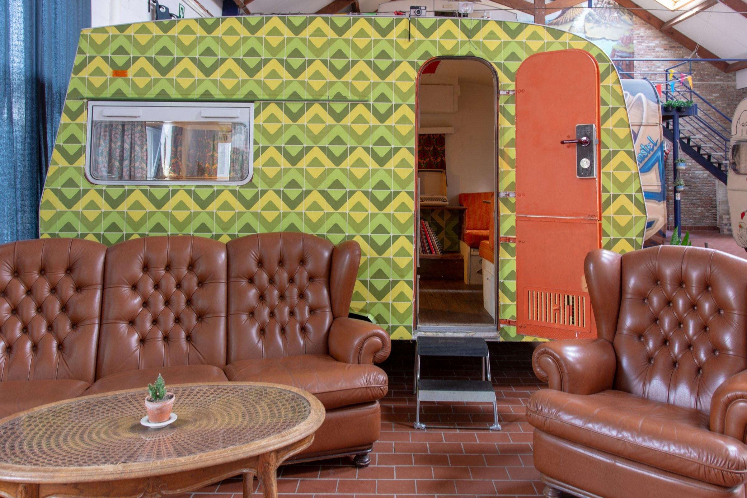Een caravan met groen druk motief en een leren bankstel voor de deur.