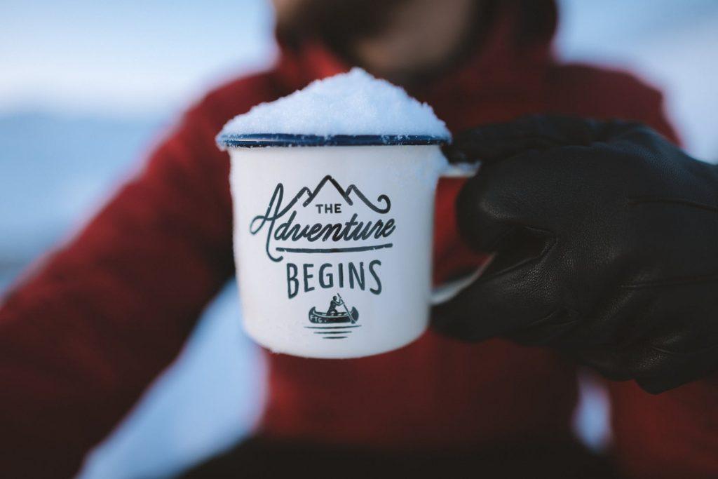 Een emaille mok met de tekst The adventure begins, gevuld met sneeuw