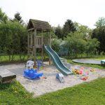 Een houten speelhuisje met glijbaan, in een zandbak omringd met speelgoed.