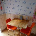 Tafel voor twee in de pipwagen, met oranje stoelen.