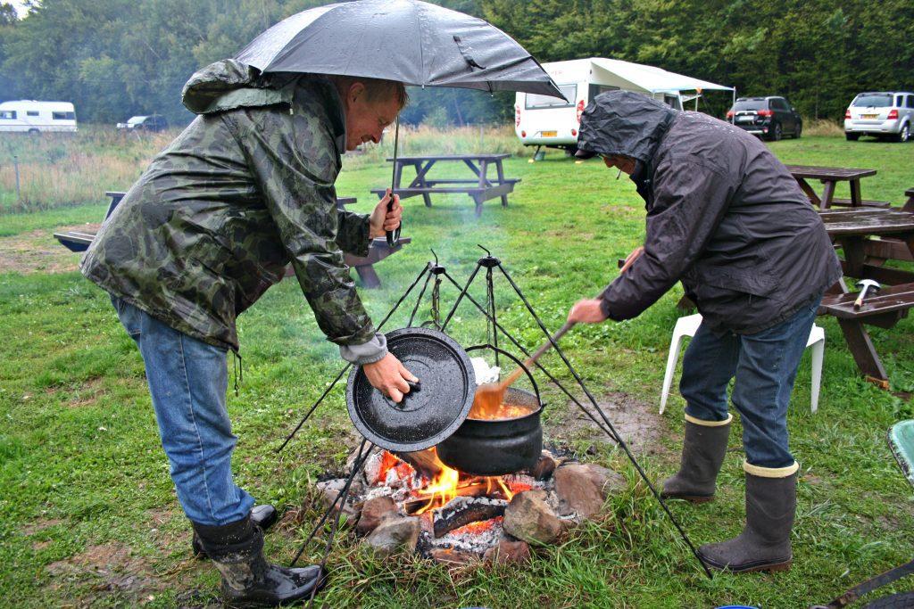 In de regen, boven een vuurtje wordt goulash gekookt in een Dutch Oven.