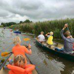 Kano's en kayak in het water, met kinderen in zwemvesten die peddelen