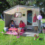 Een vrolijke caravan met luifel en twee dames die aan tafel zitten.