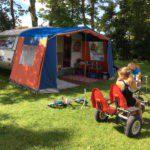 Meisje op een skelter voor de caravan met voortent.