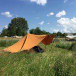 Tenten omringd door hoog gras.