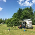 Een kleine caravan en tent op een kampeerveld.