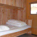 Een eenpersoonsbed aan een houten wand.