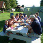 Een gezin aan de picknicktafel, pizza etend.