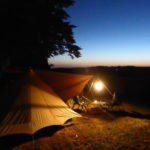 Een tent in de schemer, met en lichtje aan de scheerlijn.