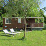 Een houten stacaravan met veranda en twee ligbedden in het gras.