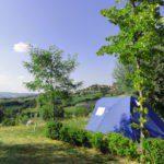 Een tent met uitzicht over de groene heuvels.