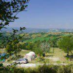Tunneltent met weids uitzicht over groene heuvels van Le Marche