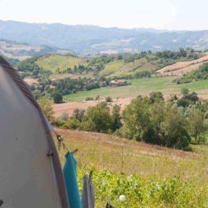 Een tent met weids uitzicht over de groene heuvels