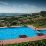 Een groot zwembad met ligbedden en een prachtig uitzicht over de groene heuvels