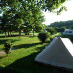 Overzicht van het speels ingerichte kampeerveld, vol heggen, struiken en bomen met hiertussen een tent en een caravan.