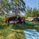 Twee ingerichte De Waard tenten op een groen kampeerveld.