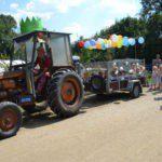 Een traktor met aanhangwagen vol kinderen en versierd met ballonnen.