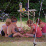 Vijf kinderen zitten in de schaduw op het gras te spelen