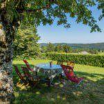 Een tafel met stoelen, met uitzicht over de groene heuvels.