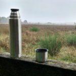 Een thermoskan op een houten biels, met uitzicht over de heide.