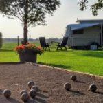 Een jeu de boulesbaan met ballen, met de op de achtergrond een caravan en weids uitzicht.