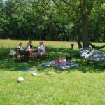 Onder een boom in de schaduw hang een hangmat, picknicken kinderen en zitten ouders aan tafel.