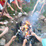 Kampvuur en allemaal handen die stokjes met marshmallows vasthouden.