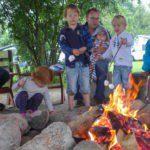 Vader met kinderen warmt marshmallows boven het kampvuur.