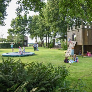 Een groot speelveld vol kinderen, met een speelfort, zandbak en trampoline