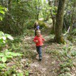 Twee kinderen rennen over een bospad.