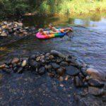 Twee meisjes liggen in een bootje en varen op de dordogne, bij een dam van keien.