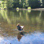 Een meisje zit in een kampeerstoel in rivier de Dordogne.