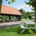 Een picknicktafel voor de overdekte kampvuurplaats.