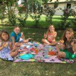 Vier meisjes aan het picknicken op een kleedje in het gras.