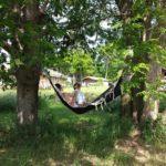 Moeder en dochter in een hangmat tussen twee bomen, met op de achtergrond de safaritenten