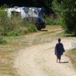 Een jongetje met een handdoek om van achter, loopt richting de tent.
