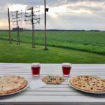 Twee pizza's op tafel, met uitzicht over de groene landerijen.