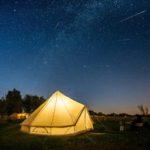 Een Bell tent in het donker, van binnenuit verlicht. Heldere lucht met vele sterren