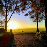 Een hek bij de oprit van de camping, met felle zonsopkomst op de achtergrond.