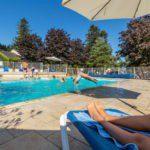 Een omheind zwembad met spelende kinderen en mensen op ligbedjes.