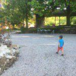 Een jongetje loopt over het grind van de binnenplaats, omringd door groen.