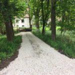 De entree met een lange oprijlaan van wit grind met aan de zijkant grote groene bomen.