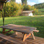 Op de voorgrond een picknicktafel en aan de andere kant van het groene kampeerveld een safaritent