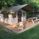 Een safaritent op een vlonder met een terras met zitje en picknicktafel